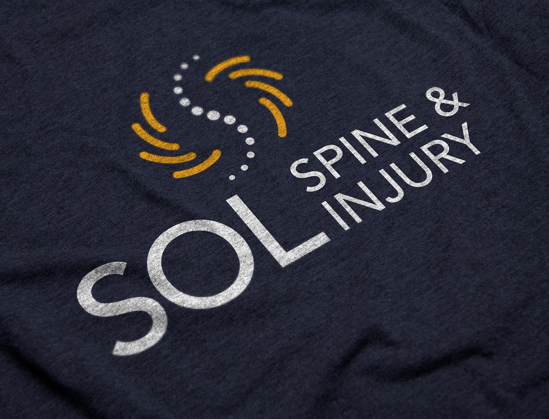 SOL Spine & Injury logo design on a navy blue T-shirt